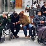 Dos señoras dependientes, acompañadas de sus cuidadoras, en una plaza del centro de Madrid. FERNANDO SÁNCHEZ ECONOMÍA FEMINISTA