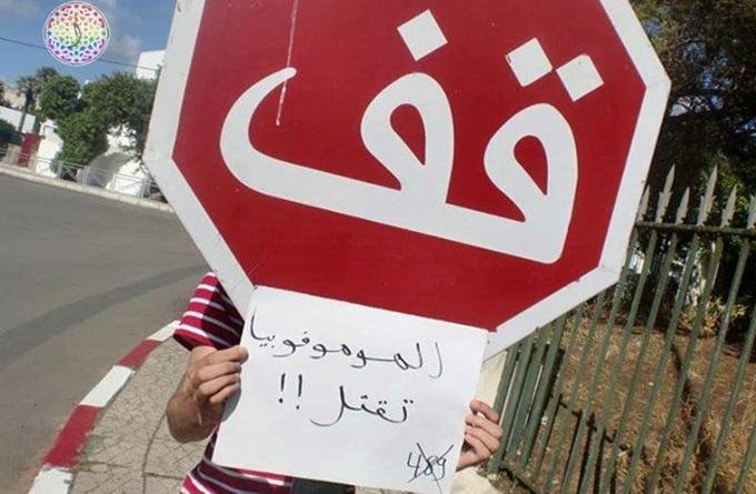 """Un joven coloca un cartel bajo una señal de 'stop' en el que se lee """"la homofobia mata""""."""