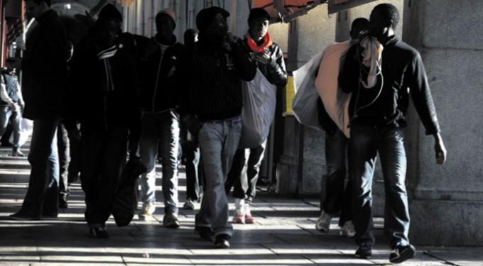 Varios manteros caminan por los soportales de la Plaza Mayor de Madrid. FERNANDO SÁNCHEZ