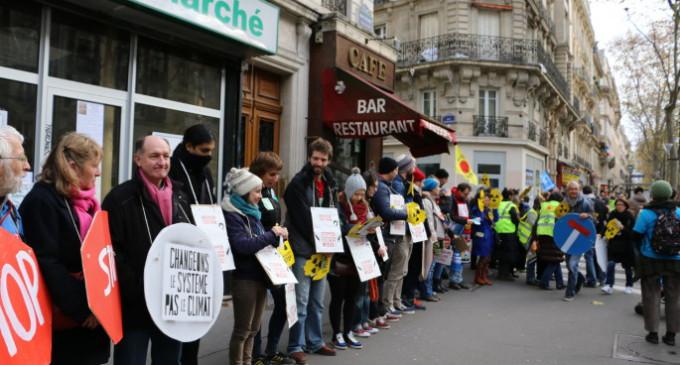 Una cadena humana desoye la prohibición y se manifesta por el clima en París