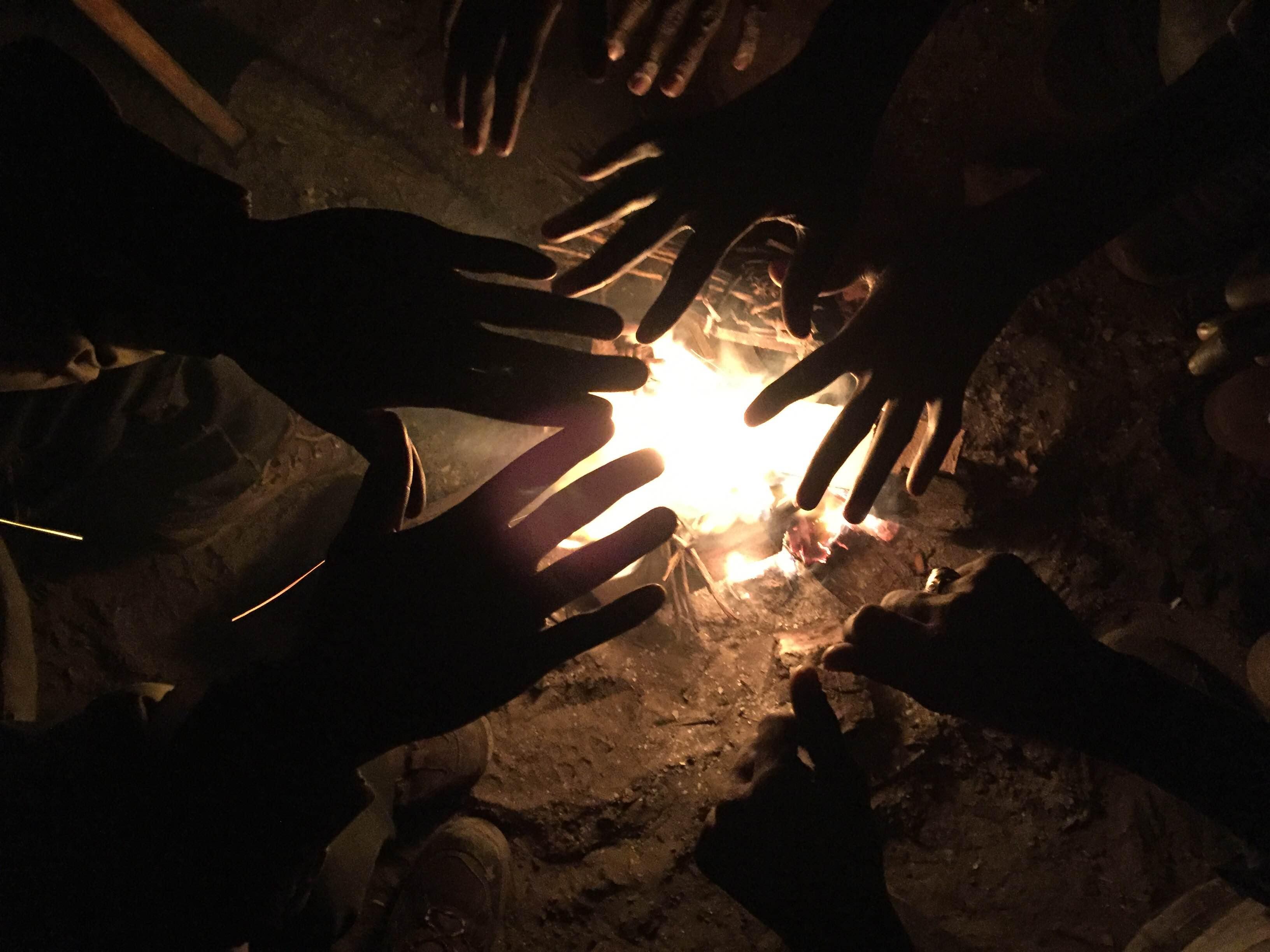 Manos de refugiados sobre el fuego, en la Jungla de Calais. FOTO: JOSÉ BAUTISTA.