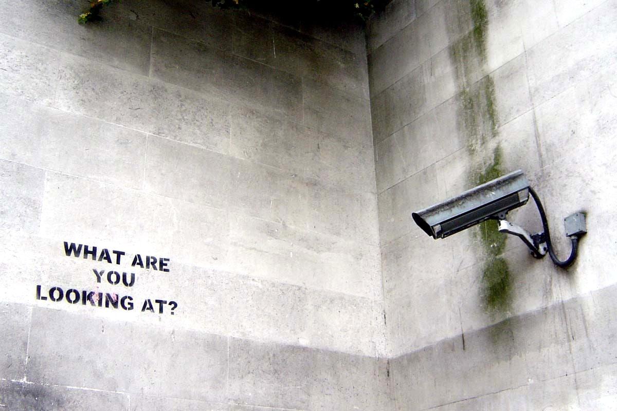 Graffiti de Banksy frente a una cámara de circuito cerrado.