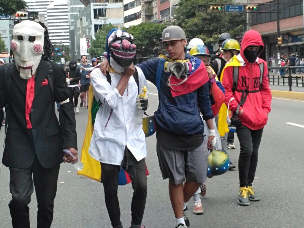 Jóvenes con máscaras antigás durante una protesta en Caracas. Foto: Manuel Rueda/Agência Pública.