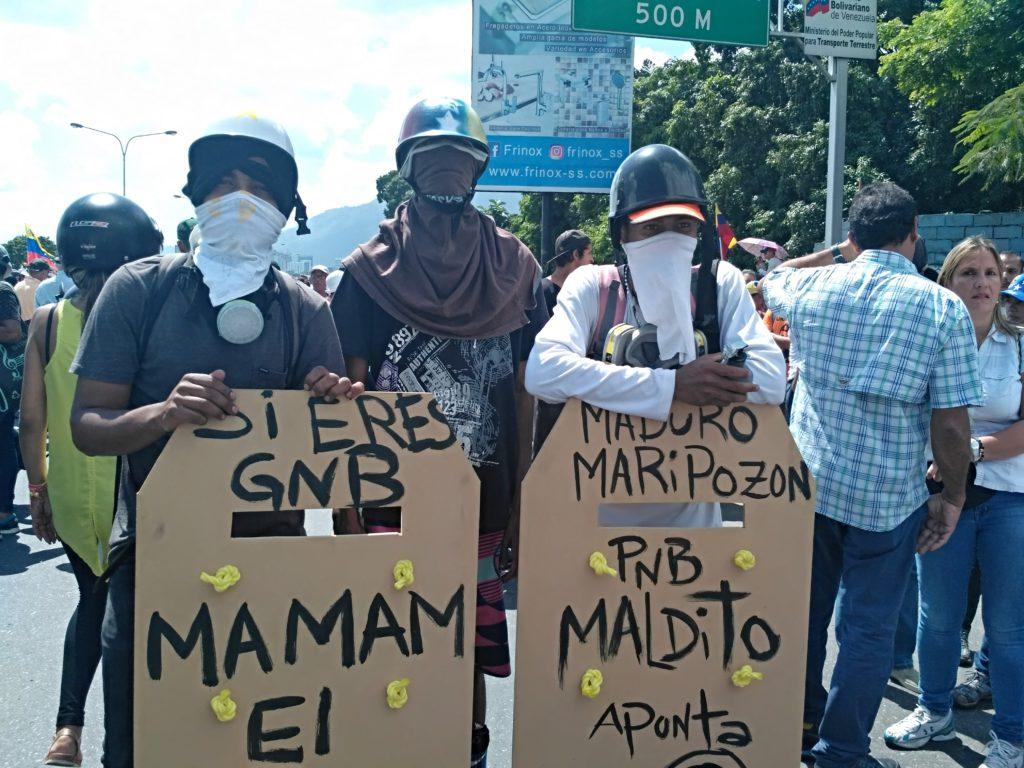 Manifestantes con escudos tallados en madera. Foto: Manuel Rueda/Agência Pública.