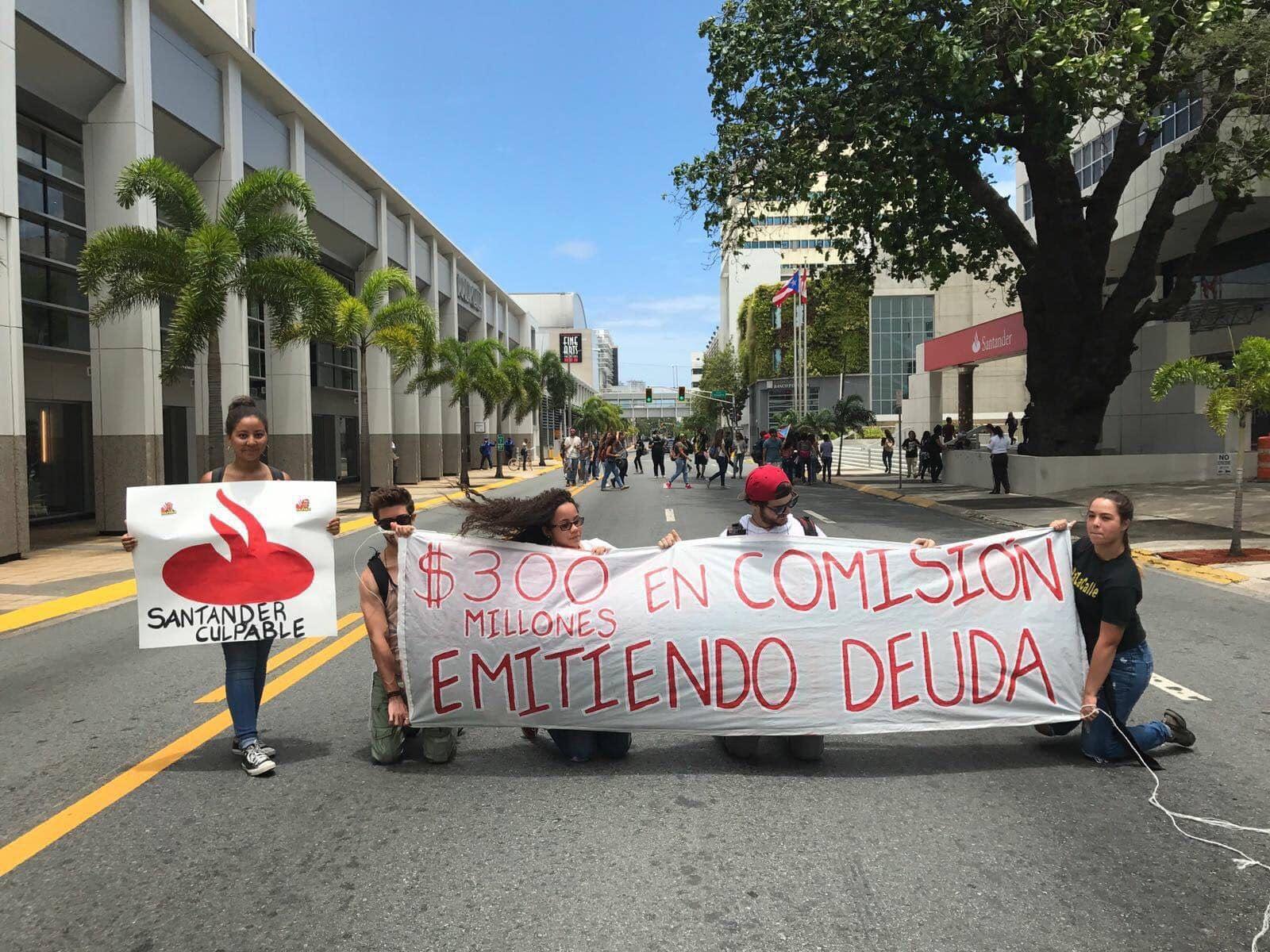Un grupo de estudiantes sostiene una pancarta contra el Banco Santander en San Juan, Puerto Rico. Foto: David Galarza.