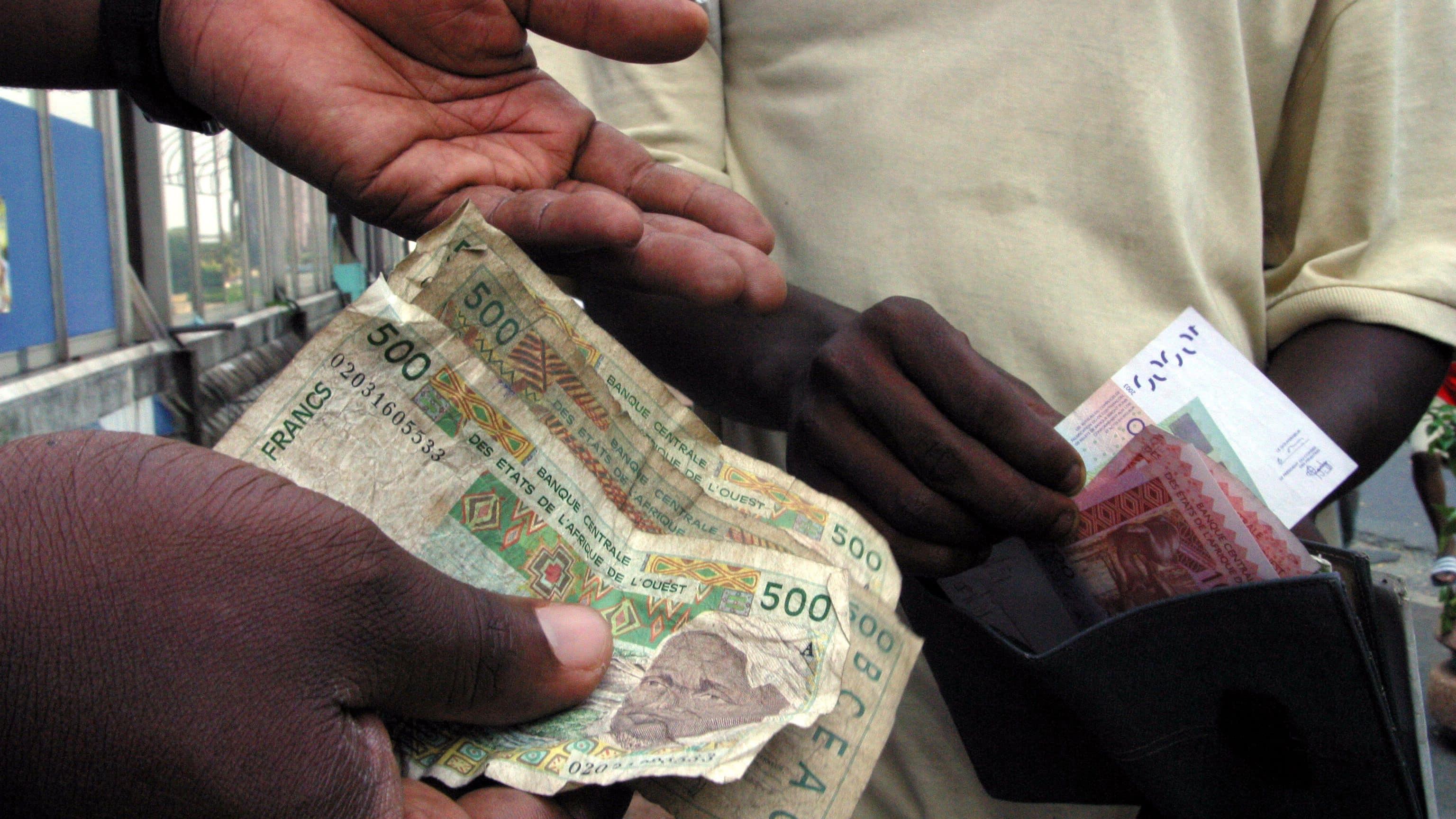 Dos hombres intercambian billetes de francos CFA. Foto: Thierry Guegnon PW/SM.