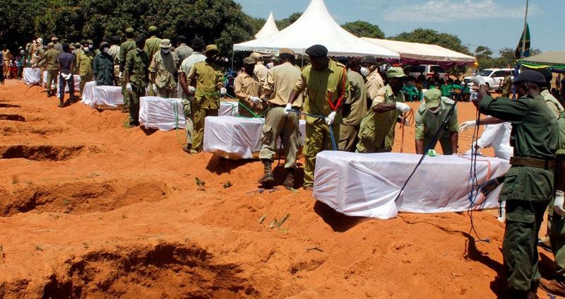 Los agentes de seguridad de Tanzania se preparan para enterrar los ataúdes que contienen los cuerpos de los pasajeros recuperados después de que el transbordador MV Nyerere se volcó frente a las costas de la isla de Ukara en el lago Victoria