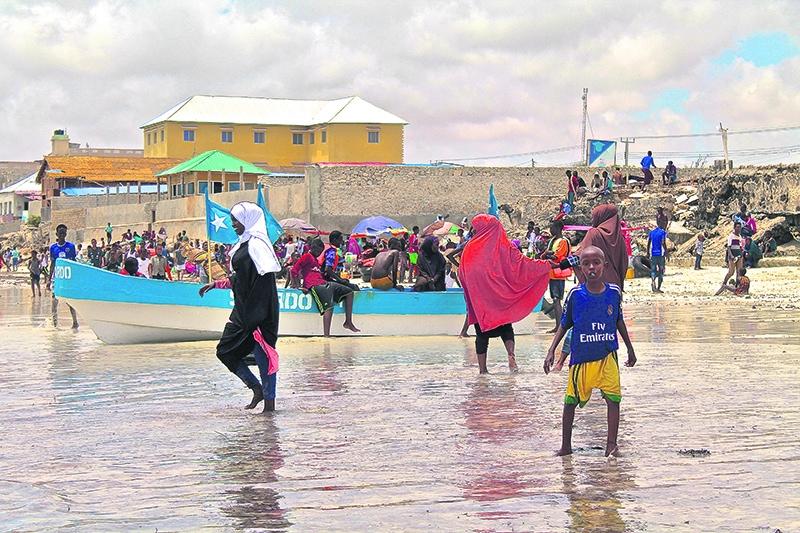 Mujeres y niños pasean por la playa de Liido. P. L. O.
